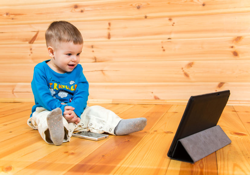 38001055 - excited baby boy watching his tablet computer sitting on the floor